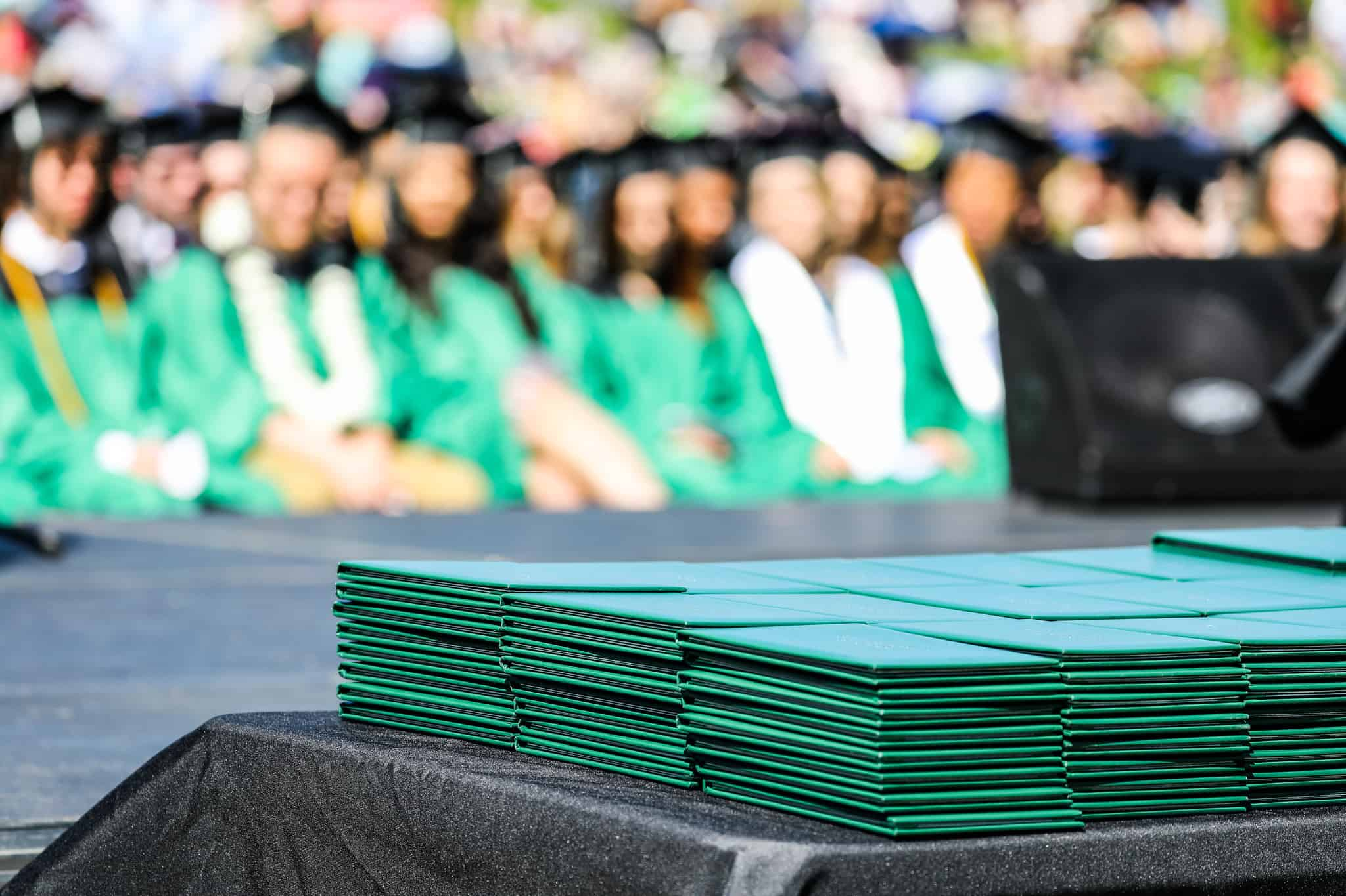 students at graduation with diplomas on a table